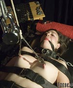 Sexy Brunette gets put into heavy leather and chain bondage, weights added to her nipple clamps and mummified in saran wrap