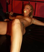 Tanned and Tattooed blonde is strapped down, ball-gagged and given a fearsome whipping